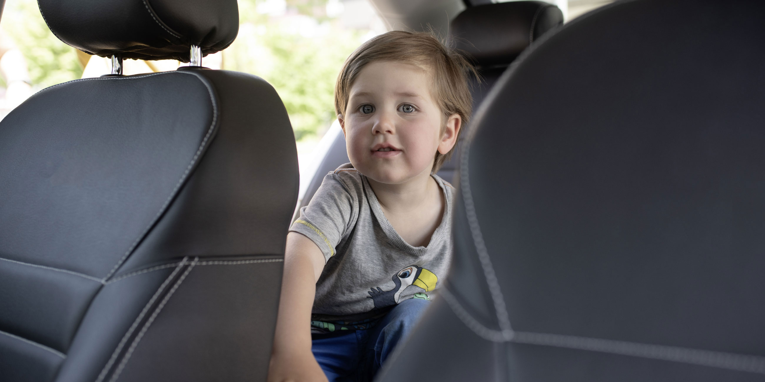 A small boy sits in the backseat of a TaxiPlus and smiles into the camera.