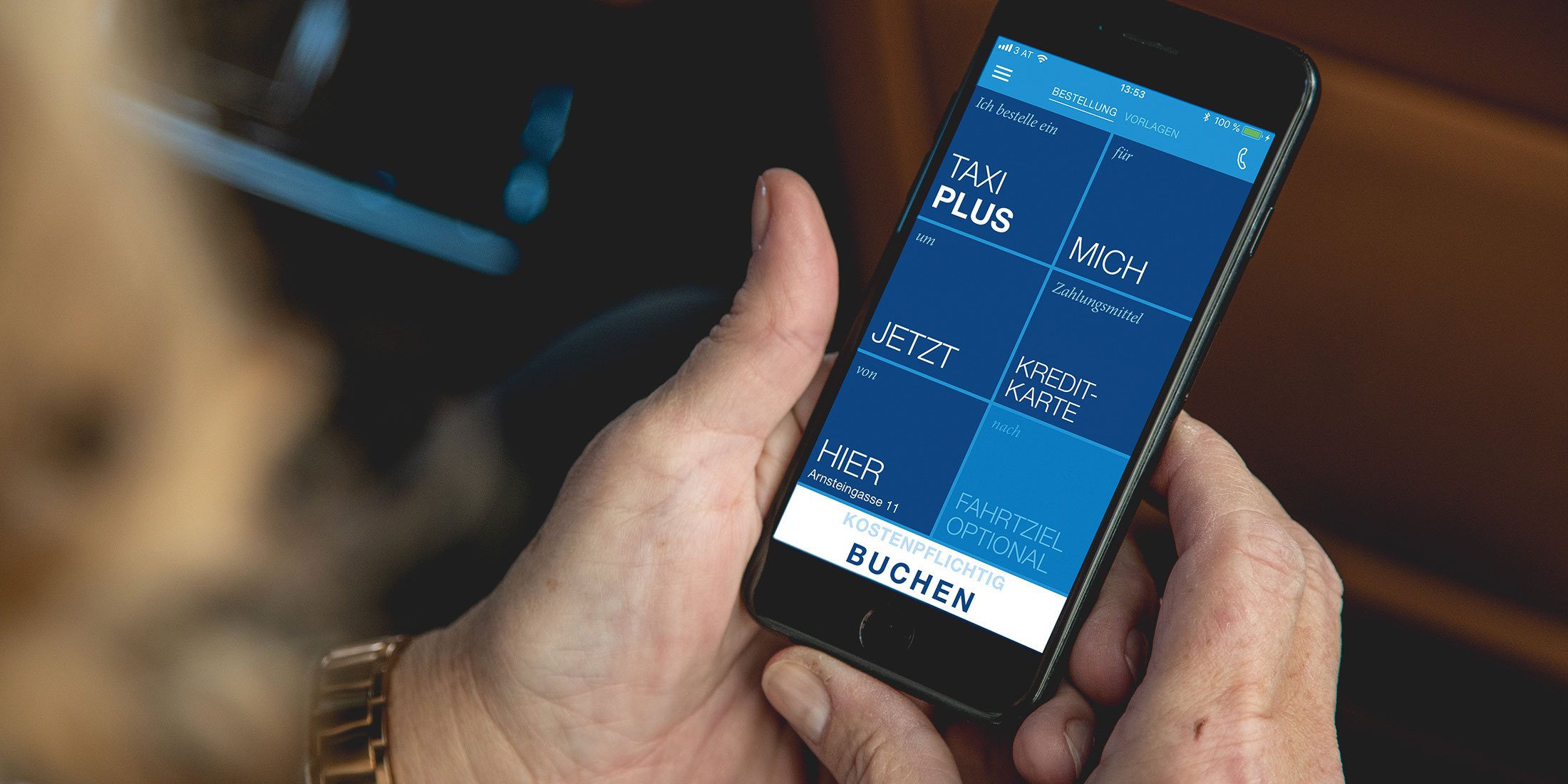 Der Home Screen der TaxiPlus App ist am Display eines Handys zu sehen, welches von einer älteren Dame gehalten wird.