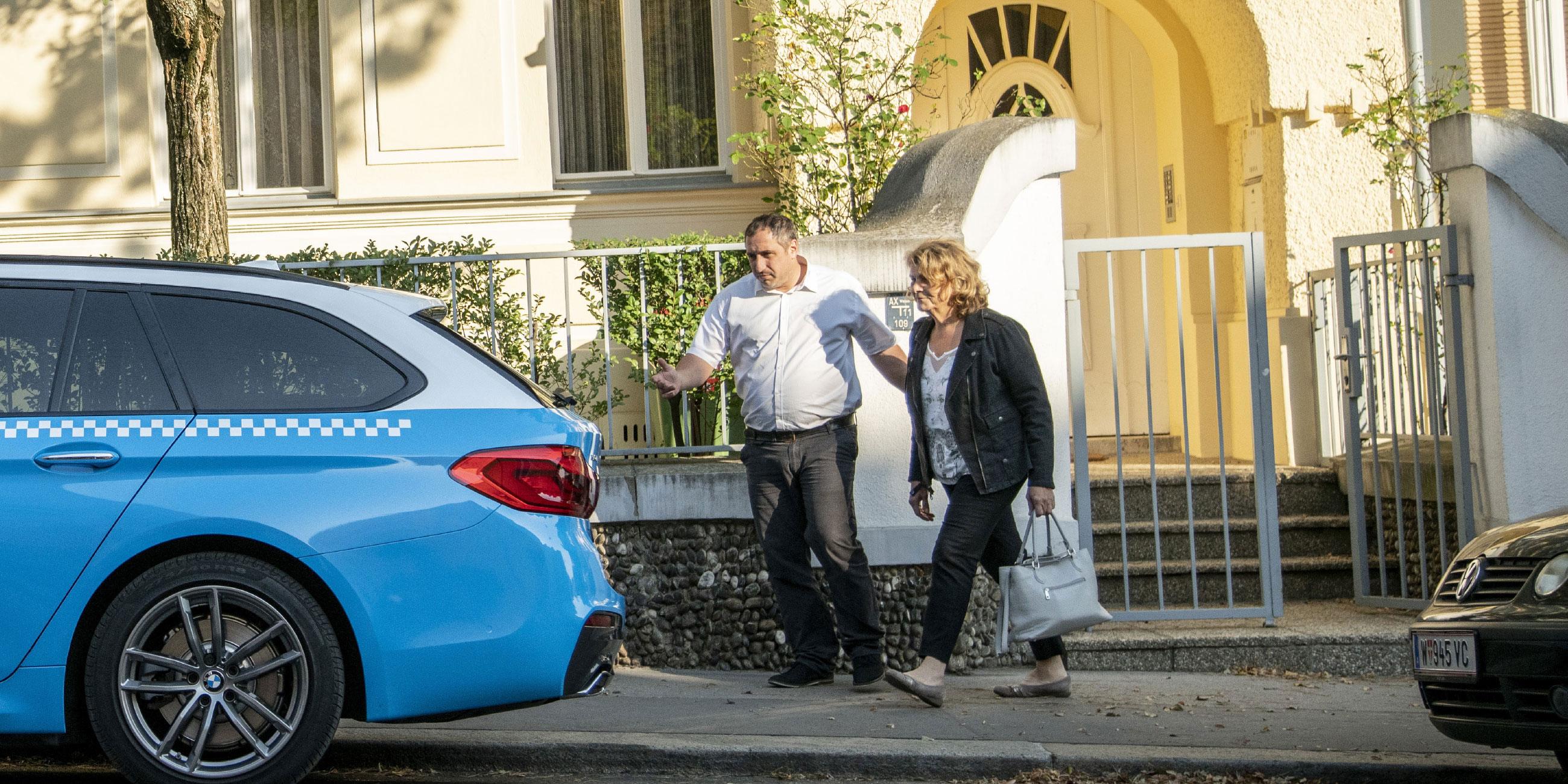 Ein TaxiPlus Lenker begleitet eine Seniorin zum TaxiPlus Fahrzeug.