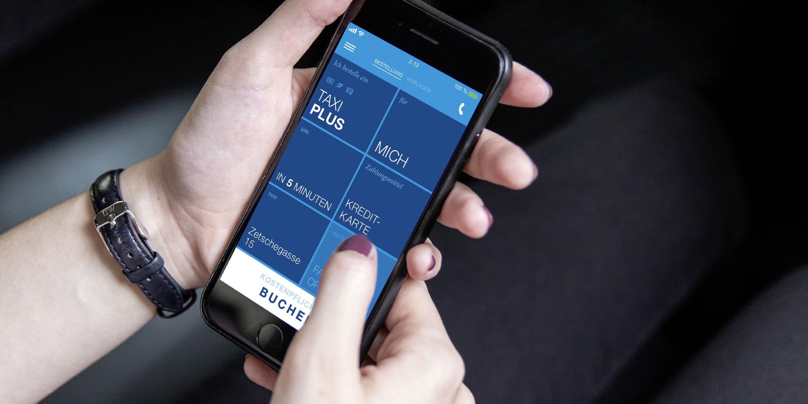 Der Home Screen der TaxiPlus App ist am Display eines Handys zu sehen, welches von einer Frau gehalten wird.