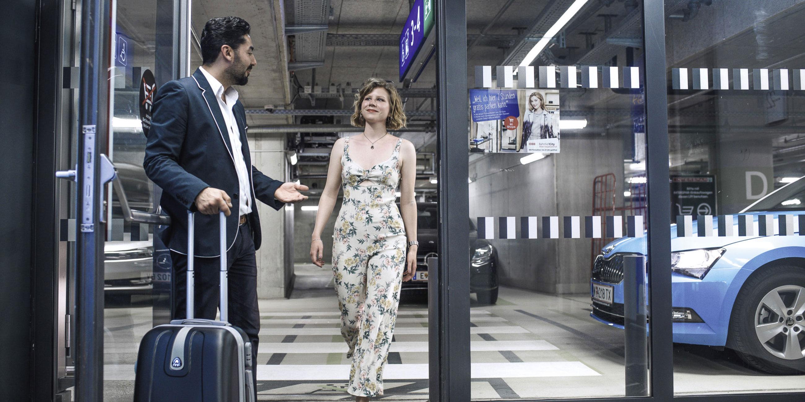 Der TaxiPlus Lenker hält einer jungen Frau am Hauptbahnhof die Tür auf, während er ihren Koffer trägt.