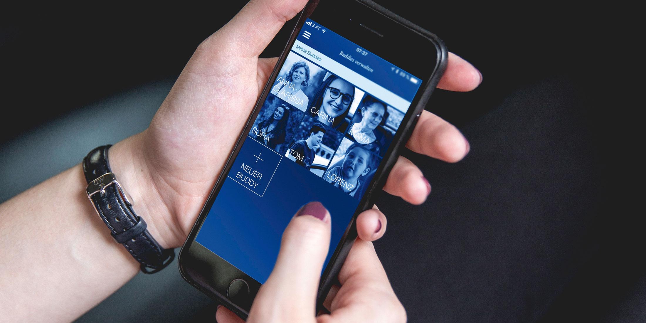 Der Buddy Screen der TaxiPlus App ist am Display eines Handys zu sehen, welches von einer Frau gehalten wird.
