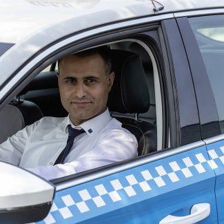 Ein TaxiPlus Lenker sitzt am Steuer eines TaxiPlus Fahrzeuges und blickt in die Kamera.