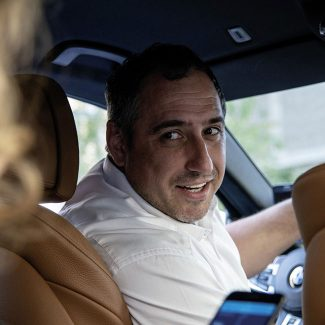 Ein TaxiPlus Lenker sitzt am Steuer eines geparkten TaxiPlus Fahrzeuges. Er redet mit dem Fahrgast, welcher auf der Rückbank sitzt.