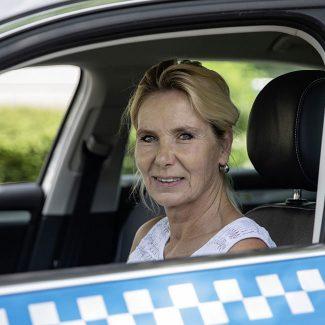 Eine TaxiPlus Lenkerin sitzt im TaxiPlus und lächelt in die Kamera.