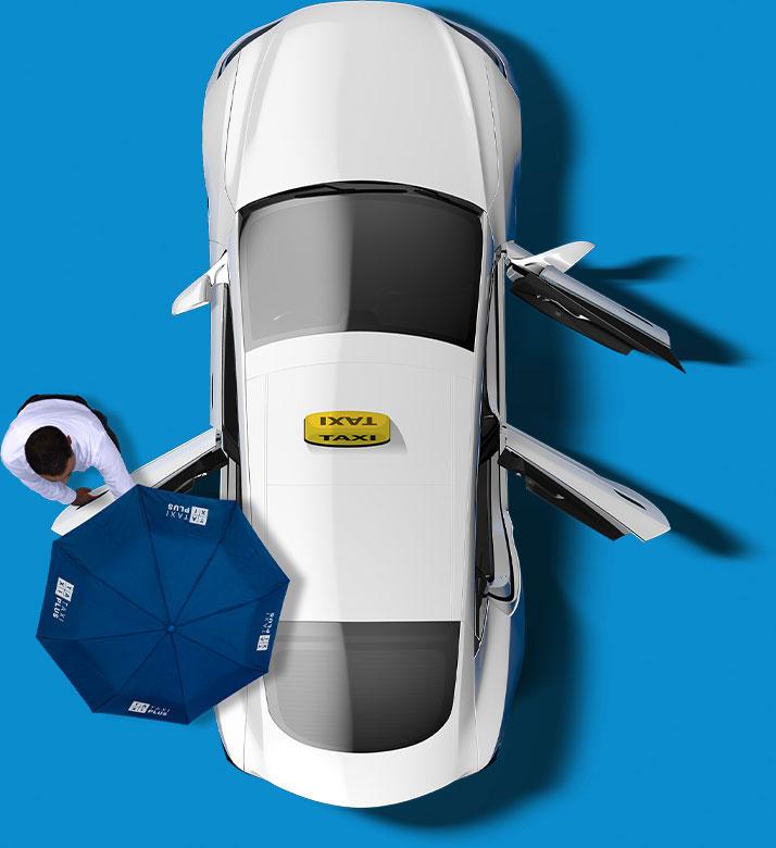 Ein TaxiPlus ist aus der Vogelperspektive zu sehen. Sowohl Beifahrertür als auch beide Hintertüren sind offen. Ein TaxiPlus Lenker hält eine der Hintertüren auf, während er einen TaxiPlus Schirm über die Tür hält.